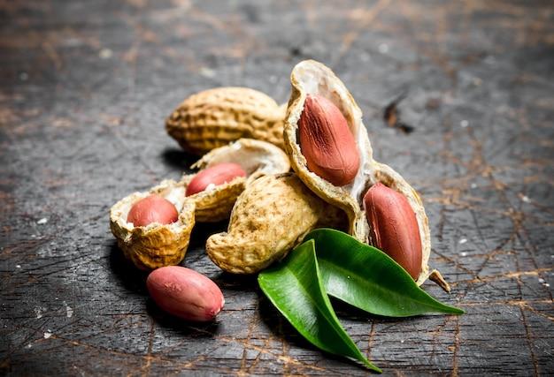 緑の葉とピーナッツ。木製の背景に。