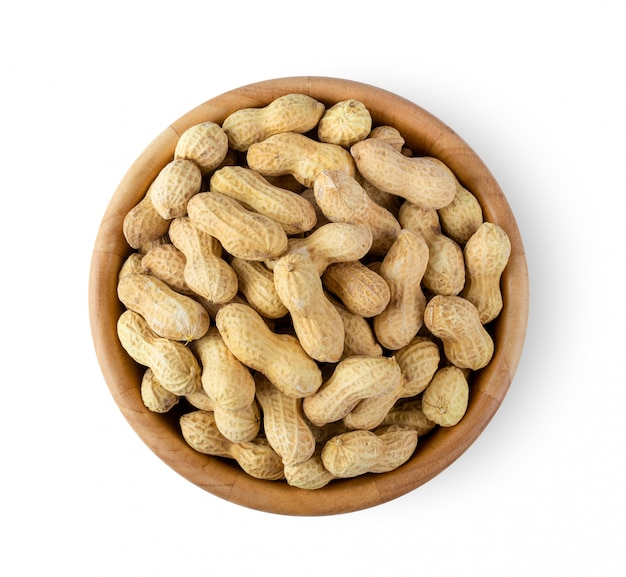 Peanuts in wood bowl on white wall.