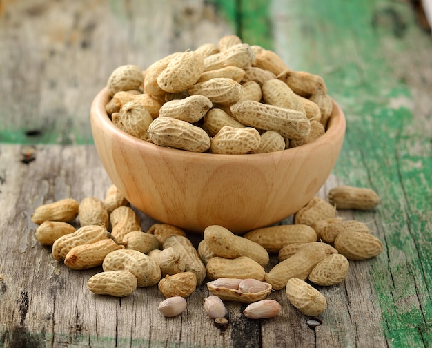 Peanuts in a wooden bowl on a wooden table
