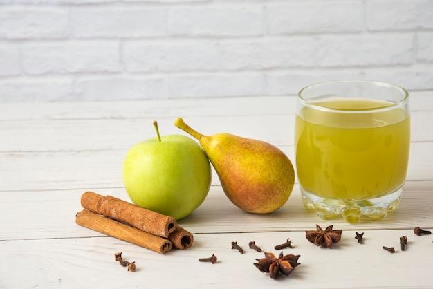 ガラスのカップにシナモン風味の梨とリンゴのジュース
