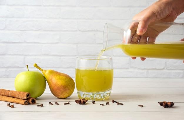 유리 컵에 계피 향이 나는 배와 사과 주스