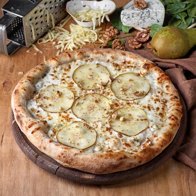 Пицца с грушей и голубым сыром, украшенная свежей рукколой на доске для пиццы, вид крупным планом