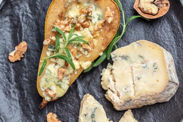Груша и сыр. груша, запеченная с голубым сыром, орехами и медом, концепция вкусного сбалансированного питания. предпосылка рецепта еды. закройте вверх.