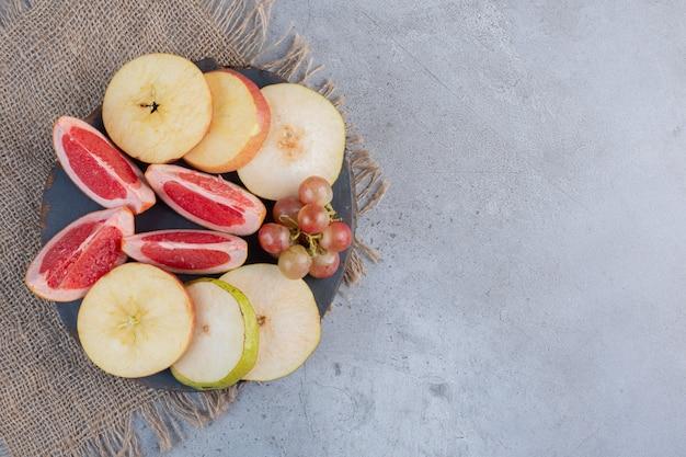 Кусочки груши и грейпфрута с небольшой гроздью винограда на деревянной доске на мраморном фоне.