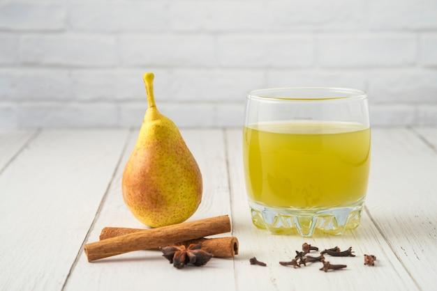 Груша и сок в стеклянных чашках на деревянном столе