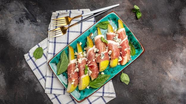 Закуска из груши с хамоном, ветчиной прошутто и голубым сыром. итальянский антипасто. баннер, меню, место рецепта для текста, вид сверху.