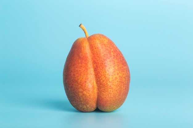 Pear on a blue background as a female body shape a metaphor of sex
