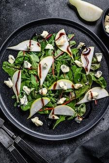 洋ナシ、ブルーチーズ、ルッコラ、ナッツのサラダを皿に盛り付けます。黒の背景。上面図。