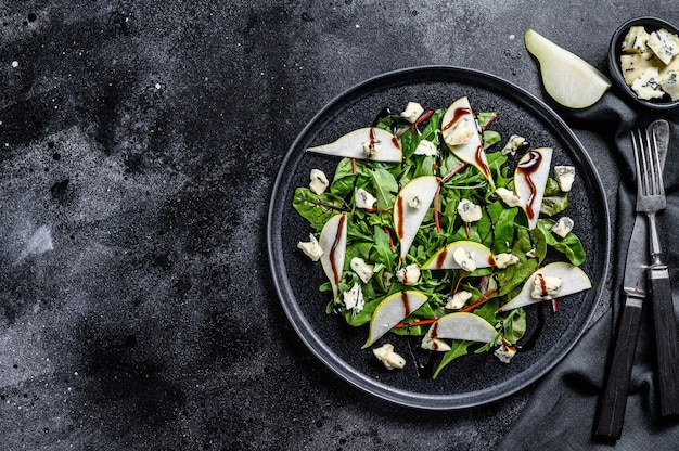 Pear, blue cheese, arugula and nut salad on plate. black background. top view. copy space.