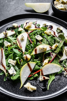 Pear, blue cheese, arugula and nut salad on plate. black background. top view