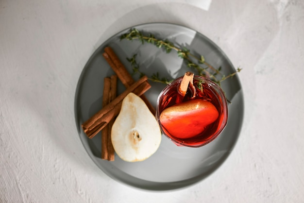 白いテーブルにラム酒、酒、梨のスライス、ローズマリー、選択的な焦点と梨のカクテル