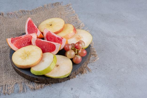Fette di pera e pompelmo con un piccolo grappolo di uva su una tavola di legno su fondo di marmo.