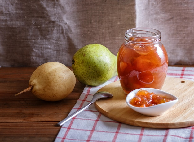 Pear jam in a glass jar on a linen tablecloth on a wooden table.