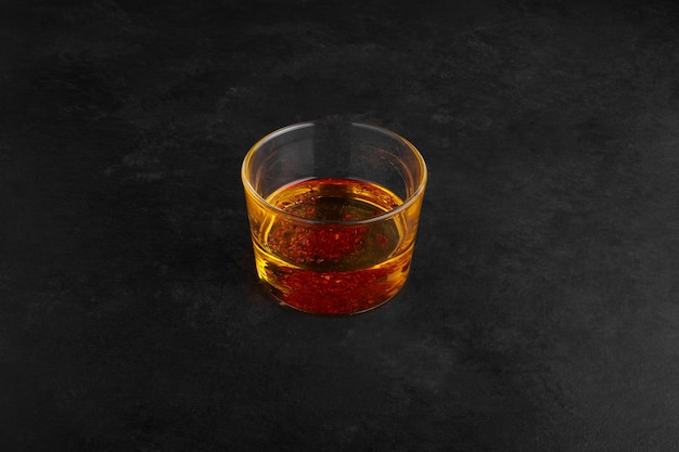 黒い表面のガラスカップに梨ジュース。