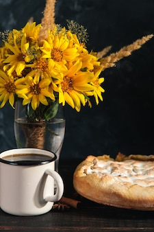 Грушевый пирог, кофе, фрукты, специи и букет цветов на деревянном темном столе. скопируйте пространство.