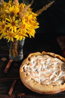 Грушевый пирог, фрукты, специи и букет цветов на деревянном темном столе. скопируйте пространство.