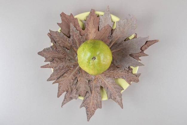 Pera su foglie di platano su marmo