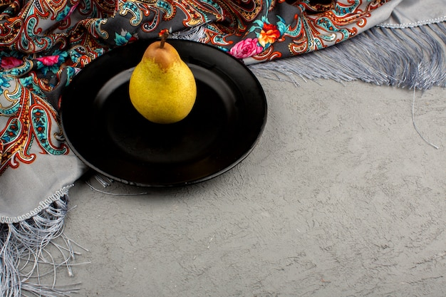 Pear ripe mellow juicy inside black plate on a grey and colorful floor