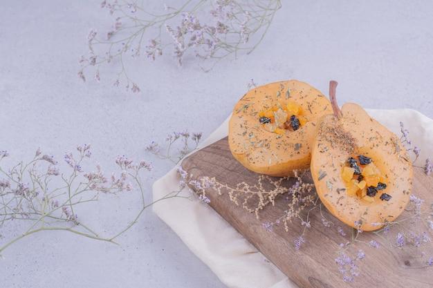 Ломтики груши с зеленью и специями на деревянной доске
