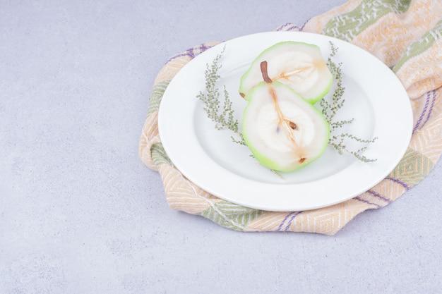 白いプレートにハーブと梨のスライス