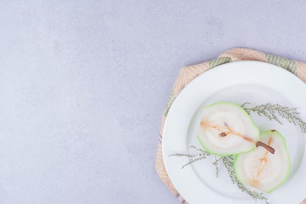 Ломтики груши с зеленью в белой тарелке