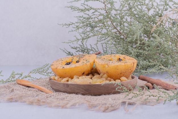Ломтики груши с султанами и палочками корицы в деревянной тарелке