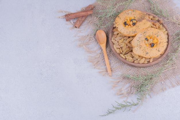 Fette di pera con uva sultanina e bastoncini di cannella in un piatto di legno