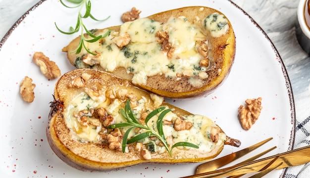 Груша с голубым сыром, орехами и медом. французская кухня. вкусный завтрак или закуска, чистое питание, диета, концепция веганского питания. вид сверху.