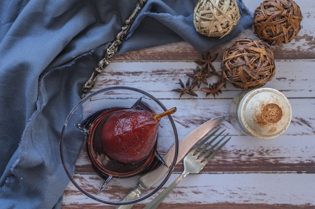Pear with red wine served in a glass bowl in rustic presentation on a wooden table. aerial view