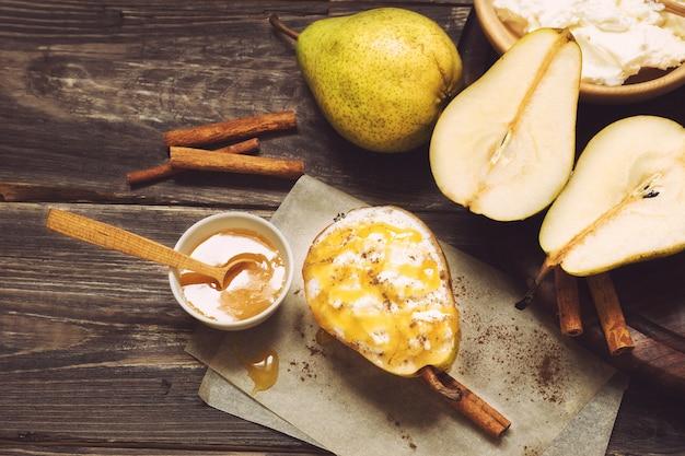 Груша с медом сыра рикотта и корицей на деревенском деревянном фоне здоровое и диетическое питание