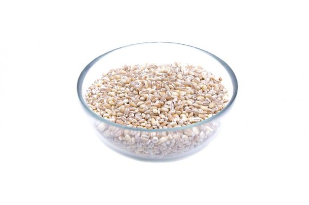 Pearl barley grains in glass jar macro close up background