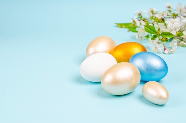 Pearl colored eggs for easter with branches of blossoming cherry on blue
