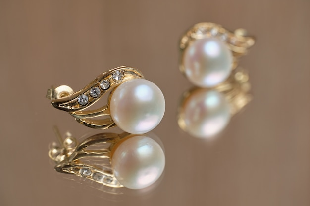 Pearl earrings on a glass table.