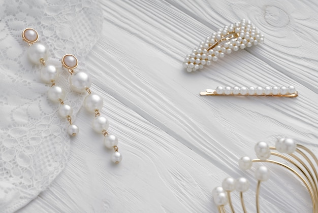 Pearl golden earrings, hairpins and bracelet on white wood