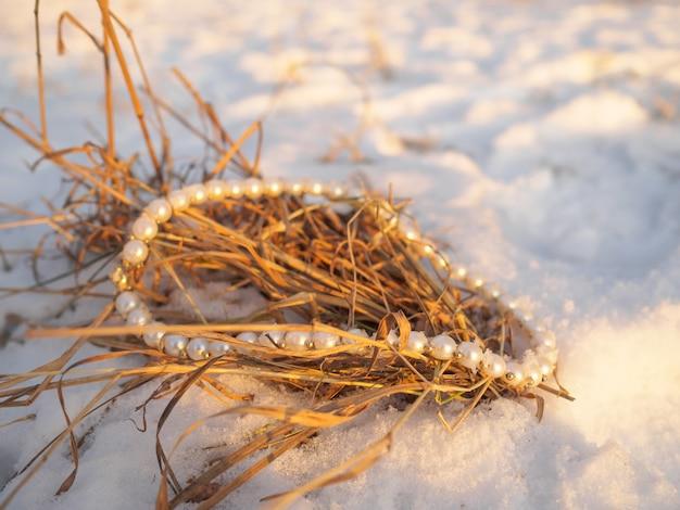 雪から突き出た乾いた草の上に横たわるパールジュエリー