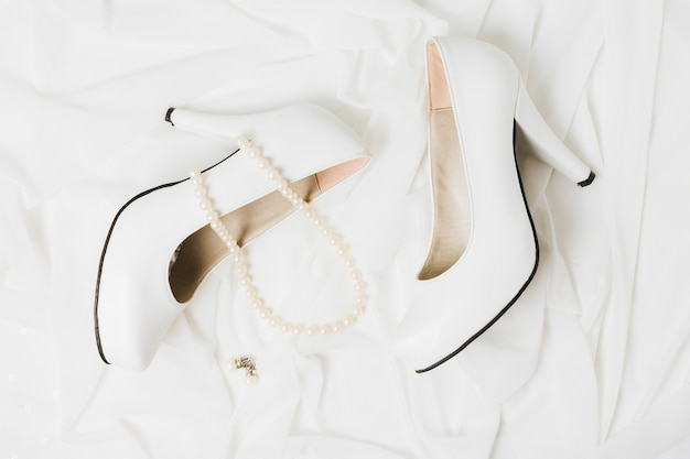Pearl necklace and earrings with pair of wedding high heels on scarf