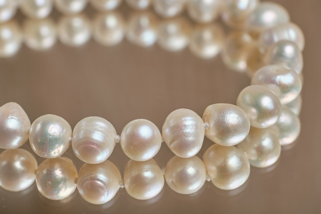 Pearl necklace on a glass table.