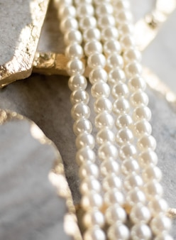 Pearl necklace on golden marble ethical jewellery  luxury background jewelry as a gift concept pearls are girls best friends