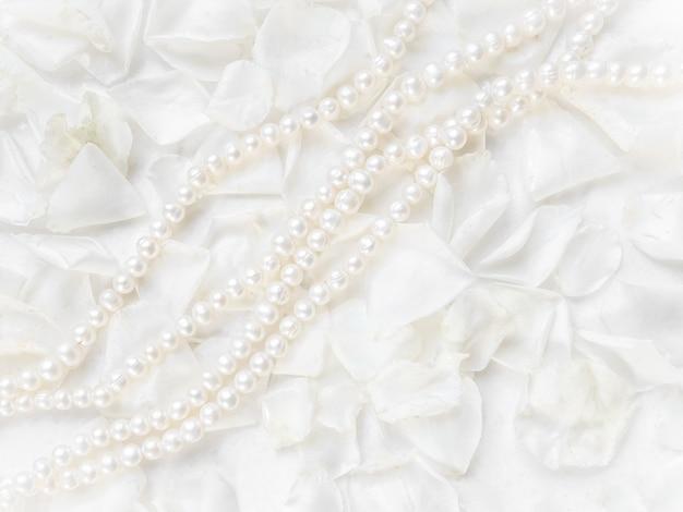 Жемчужное колье на фоне лепестков белой розы идеально подходит для поздравительных открыток