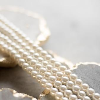Жемчужное ожерелье на золотом мраморе этические украшения роскошные фоновые украшения в подарок концепция жемчуг - лучшие друзья девушек