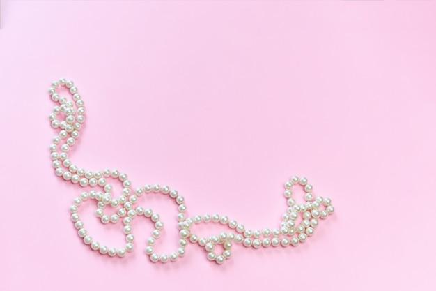 Жемчужное ожерелье на розовой поверхности