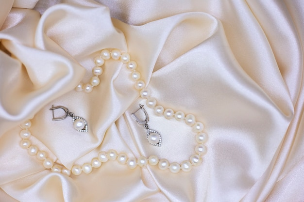 Pearl necklace and pearl earrings on beige silk top view jewelry for the bride