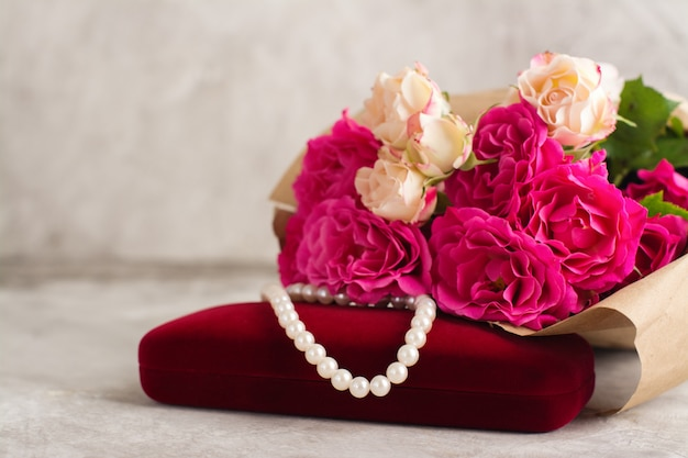 Pearl necklace and roses bouquet