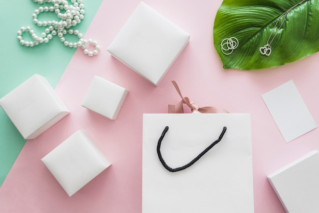 Ожерелье из жемчуга и множество белых коробок с сумкой на розовом фоне