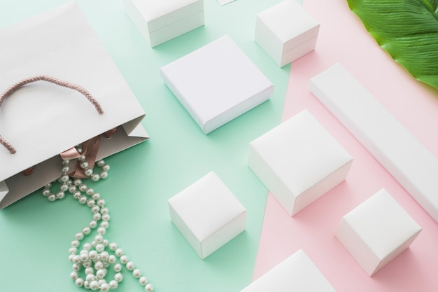 Pearls necklace falling from shopping bag with white boxes on pastel background