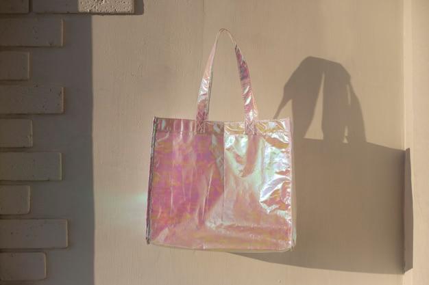 화창한 날 흰색 배경에 진주 홀로그램 가방이 공중에 떠 있습니다.