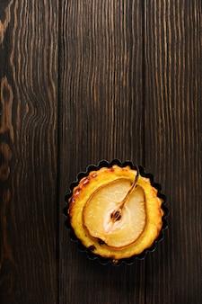 어두운 갈색 나무 오래된 테이블에 배와 커스터드 미니 타르트