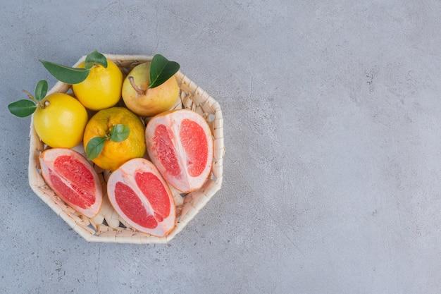 Груши и дольки грейпфрута в белой корзине на мраморном фоне.