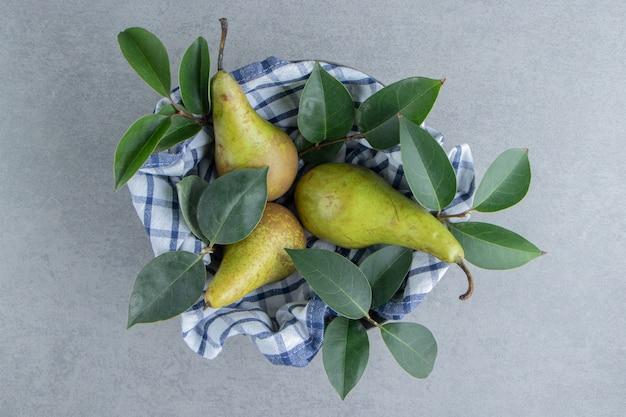 Груши и листья в миске, накрытые полотенцем на мраморе