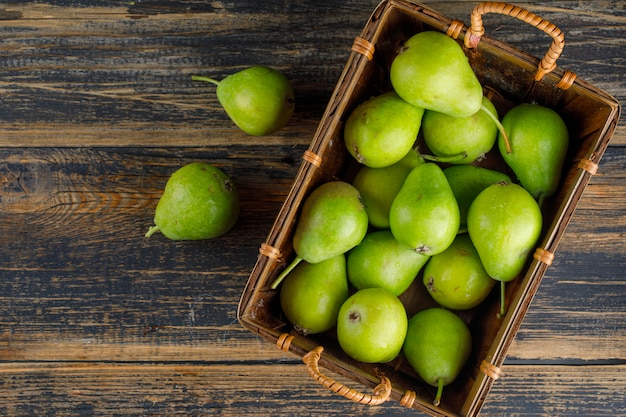 Pears in a basket top view on a wooden table